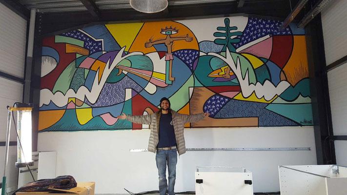 Nils devant sa fresque à Pamiers dans les locaux de APY ART