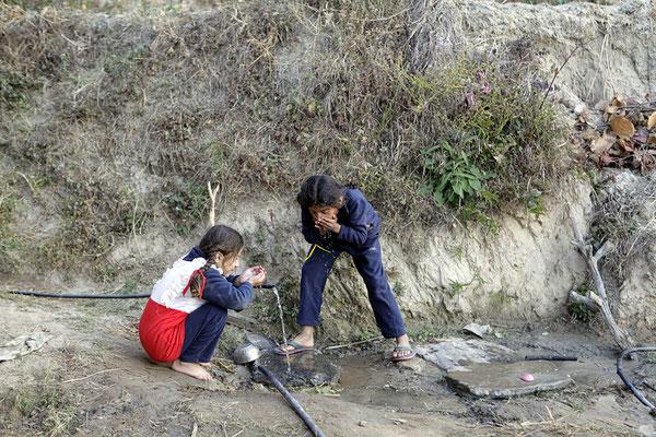 Die beiden Töchter an der Wasserstelle neben dem Haus