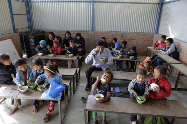 Die Kinder mit Lehrer Mr. Luitel am Essen