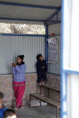 Kind im Unterricht mit der Hilfs-Lehrerin Kalpana Miss.