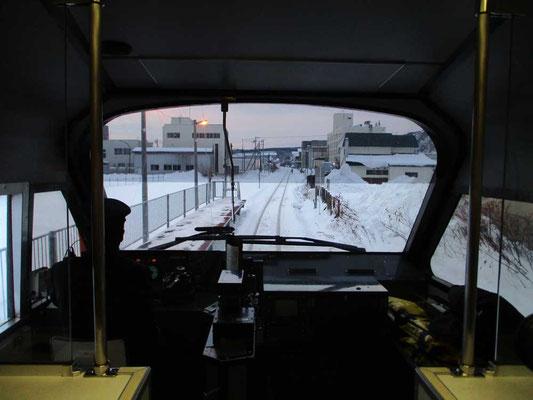 発車前、展望車最前にて運転士さんの後ろ姿と一緒に前方を見ます ビルの影から朝日が昇ろうとしています
