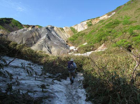最初は荒々しい様子の谷を残雪を越え登っていく