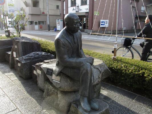 腰掛けて通りを見つめている人 シンボルの帽子が向こう側に置いてあります
