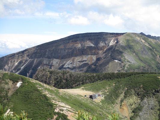 同じく巨大な爆裂口の硫黄岳をバックに、手前鞍部には根石岳小屋が見えます この小屋には何度か泊まったことがありますが、何故かこんな場所なのに風呂があるのです 沢の源頭で水が出るのです