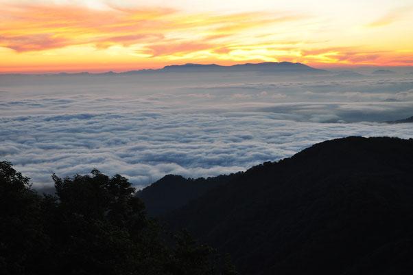 輝く空と雲海の上に稜線が見える朝日連峰