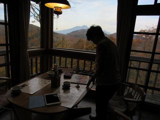 宿泊先の食堂から夕日の妙高山をスケッチしている