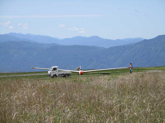 着陸後、割りと普通の格好をした人が二人降り立ち、自分たちで羽根を支えて運んでいます 軽そう?