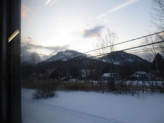 川湯温泉駅を通過したところ 硫黄山(アトサヌプリ)が車窓から見える 白い煙?をモクモクと吹き出しモロ活動中