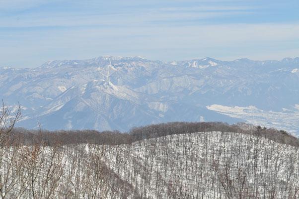 落葉樹で透けた山稜のむこうは志賀高原の山々