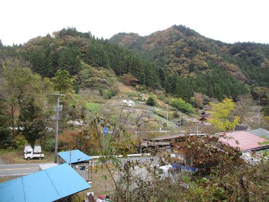 バス停から車道を少し登ると向こうに南斜面を利用した畑や民家が見える 谷あいの村落の景観