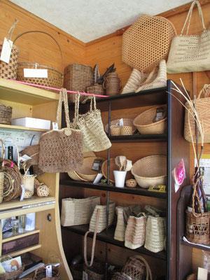 上の壁にかかっている蜂の巣のようなきれいな網目のザルはマタタビで編んだ「メイケイザル」と呼ばれているもの ぶら下がっている赤っぽい手提げかばんはアカソ 手の部分は丈夫なシナ皮 棚にはシナ皮やアカソ、ヒロロで編み込んだバッグが並んでいます