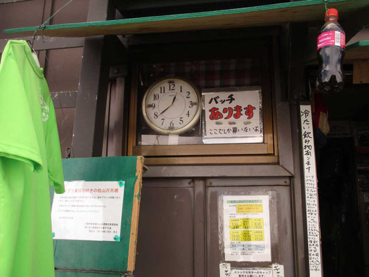 本山小屋の壁にはまっている時計 そしてバッチなどの宣伝看板