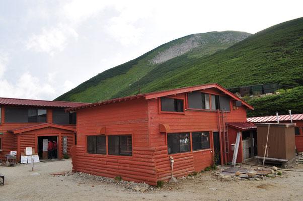 小屋脇に到着 背景には面白かった地形の双六岳が見える