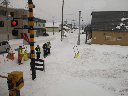 宗谷本線車窓からある踏切通過のショット 除雪作業の人たちが手を上げて列車通過の安全確認をしています