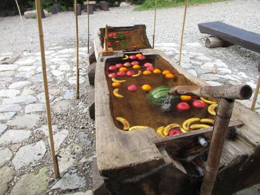 いかにも涼し気な冷水に浮かぶトマト、キュウリなど この大きな木をくり抜いた舟が見事