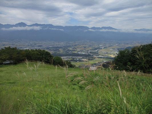 長峰山山頂の広い草原越しに正面に北アルプスが連なる