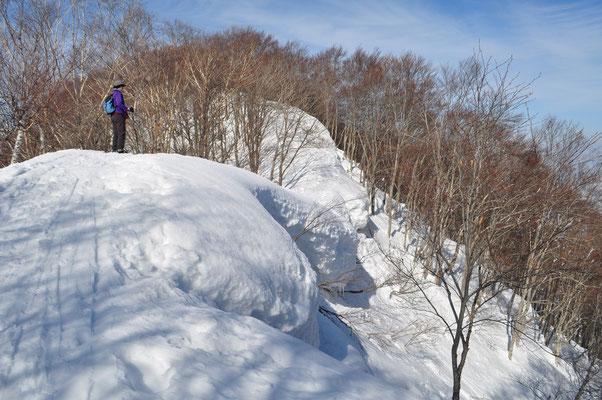 雪庇が張り出し垂れ下がっている