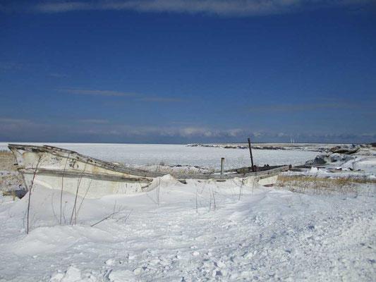 打ち捨てられた漁船も凍り、その向こうの湾内も真っ白に凍結しています