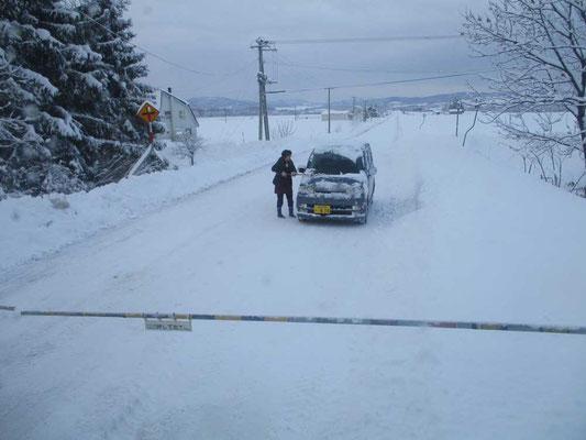 踏切で停車している車 後続車もおらず、運転手の女性は降りてフロントの除雪をして待っている
