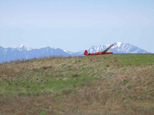 南アルプスをバックに着陸したグライダー 止まると右か左の羽根の方に傾きます
