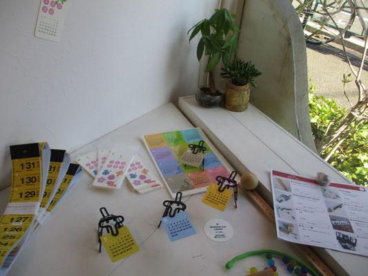 """森キヲノリさんの作品 今回も驚くような発想の""""暦""""が並びました 写っているのは立体の犬がカレンダーをくわえているもの 平面キットとして創られています"""