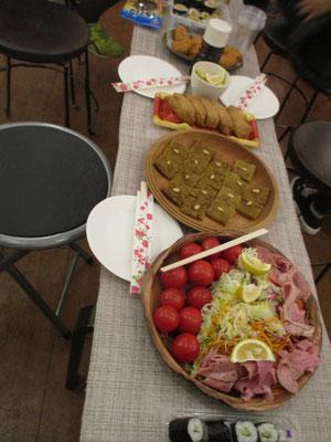 オープニングパーティーの様子1 茶色いものは小麦粉とひき肉をカレー味で焼いたもの 不思議な食感のカレー味、おいしい家庭の味