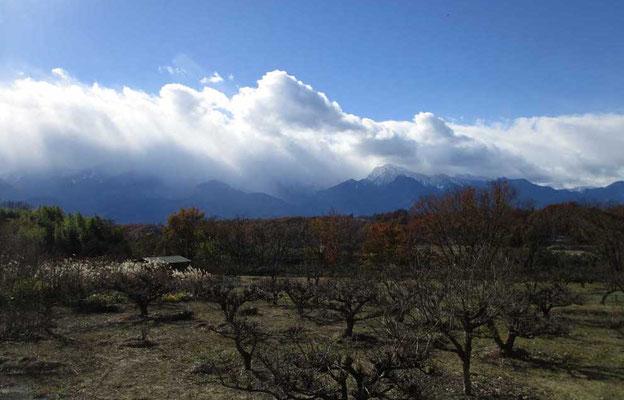 上空は青空だが、風に押された雲が高い山々を覆うようにかかる