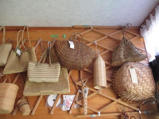左に下がっているストライプや透かしの模様入りの手提げバッグはヒロロ(学名ミヤマカンスゲ)で編んだもの、ストライプの赤味がかった線はアカソを織り込んでいる  半円形の茶の手提げ籠はアケビ