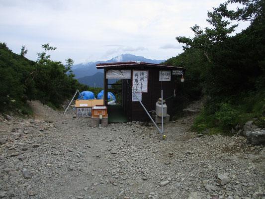外に設置されたトイレ小屋  奥に用済みの携帯トイレの回収箱があります 集めたものはヘリで下ろします