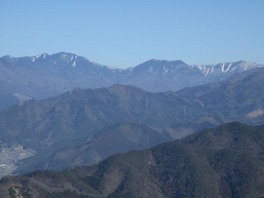 一番左の小さな三角が甲武信岳、隣のこんもりしたのが木賊山で平たいピークは破風山〜東破風山 白く線状の雪が残るのが雁坂嶺か