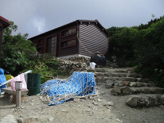 ハイマツの裏に上手いこと塩見小屋がありました 厳しい立地条件のこの小屋は大きくありません そしてトイレは携帯トイレ利用で汚物はまとめてヘリで下ろすシステムです 山では排泄物問題が水の確保と同じく最重要課題