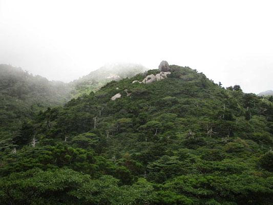 霧が流れるなかに突然見える奇岩の山