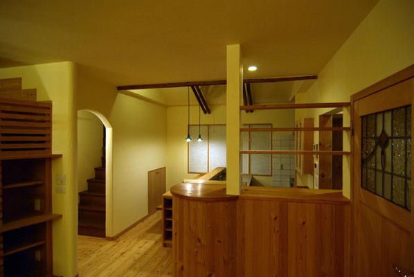 ギュッと凝縮されたような対面キッチン。cafeカウンターや壁のアーチ、丸太などRのデザインを取り入れ、遊び心のあるお店のカウンターのような空間に。