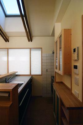 コンパクトながら使い勝手を重視したキッチン。吊戸棚にはお気に入りのグラスが飾られます。