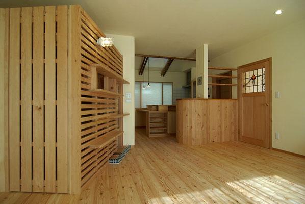 Rにデザインしたcafeカウンター越しにキッチンをみる。アンティークのステンドグラスとカウンター上部のタイルは支給品。