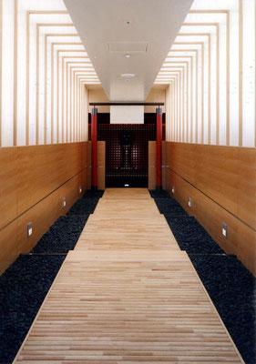 Eingang Meditationsraum: Rundhölzer massiv/Schwarze Granitsteine/Hinterleuchtetes Glas -  Foto © Knauer Architekten