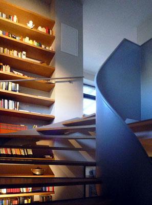 Zweigeschoßige Bibliothek entlang gewendelter Metalltreppe - Foto © Knauer Architekten