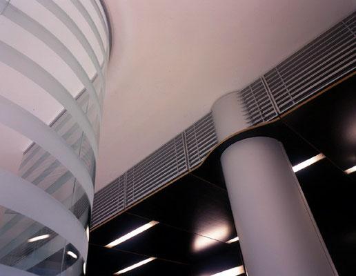 Abgehängte Decke mit stirnseitig hinter Alulamellenabdeckungen integrierten Klimageräten.