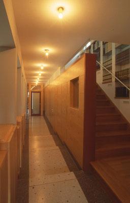 Stufenrampe zum Arbeitszimmer holzverkleideter Gangwand und integrierten Türen zu den Nebenräumen und Kellerstiege.