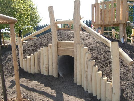 Ein mithilfe von Betonrohren und viel Holz errichteter Tobehügel mit Geländer.