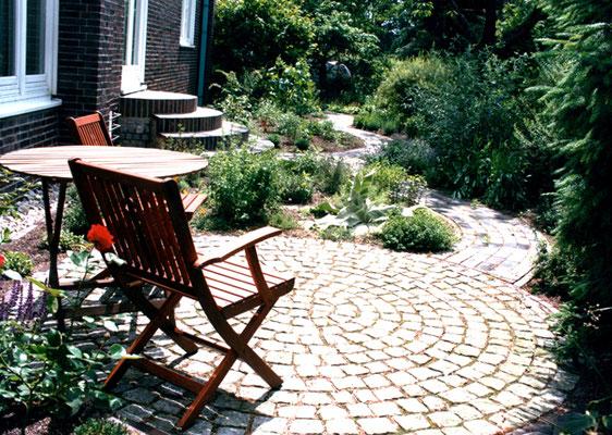 Gartengestaltung schließt nicht nur Pflanzungen sondern auch Terrassen und Pflasterarbeiten ein: eine gemütliche Sitzecke.
