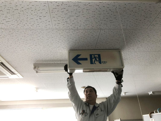 蛍光灯タイプ避難誘導灯の取り外し作業の様子