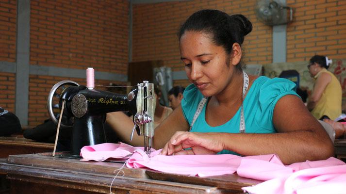 Teilnehmerin des Schneiderkurses in der Schule von MIRIAM in Estelí näht ein Kleidungsstück für ihre erste Kundin (2015). Mit dem Erwerb der neuen Kompetenzen lernen die Frauen finanziell selbständig zu werden.  © Corine Alex Gasser