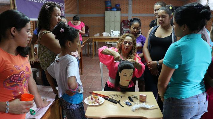 Im Frisierkurs der Escuela MIRIAM erklärt die Lehrerin, wie eine Flecht-Frisur gemacht wird (2015). Mit der Umsetzung des erlernten Wissens können sich die Frauen finanziell unabhängig und selbständig machen.  © Corine Alex Gasser