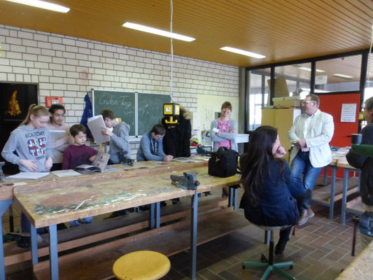 Ofenbaumeister Thomas Mann erklärt den Schülerinnen und Schülern die Wärmetechnik eines Kamin und Ofen.