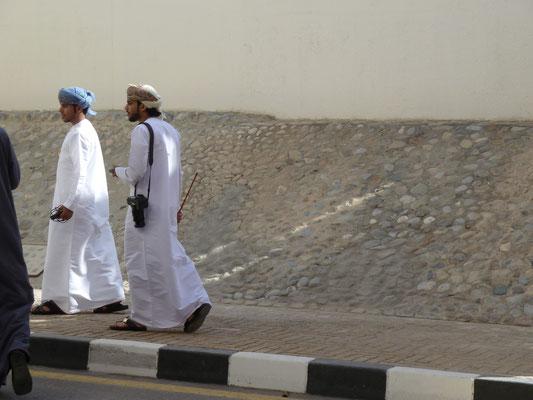 Männer in Dishdashas und mit Kamelstöcken