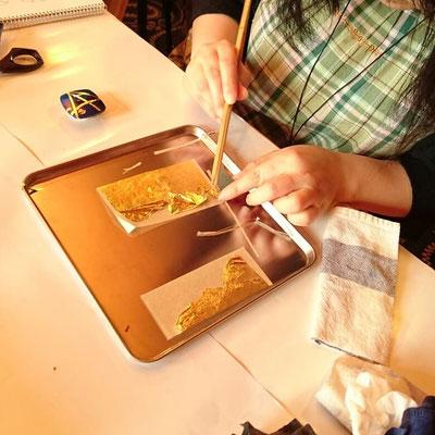 金箔を油取り紙に「あかして」、ハサミで細く切り、漆を塗った上に貼っています
