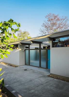 落ち着いた色合いの中にビビットな玄関ドアが特徴的。