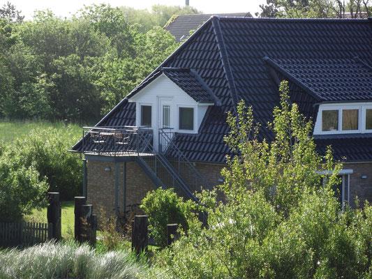 Aufgang zu Ihrer Wohnung. Dort haben Sie auch eine kleine Sitzgelegenheit mit freier Sicht über unverbaute Wiesen.