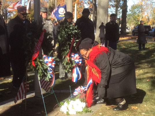 Yulanda Burgess placing the white carnations at the base of the flagpole in the Civil War section at Historic Elmwood Cemetery in Detroit